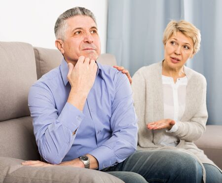 disgruntled mature couple quarreling at home with each other and take offense