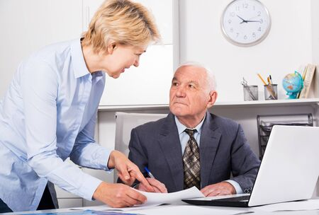 Aged male manager and female secretary working productively together in office Imagens
