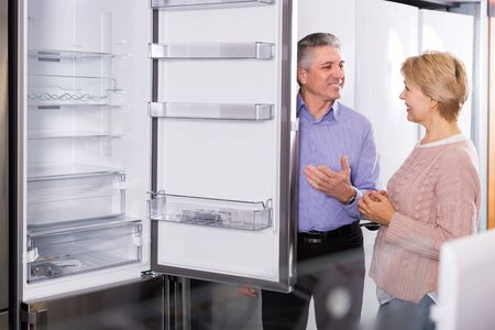 Husband and wife together choose for themselves refrigerator in center of household appliances Stok Fotoğraf