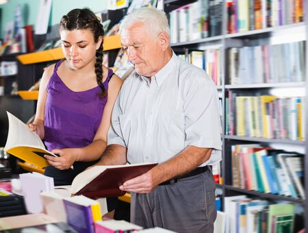 Mature man with granddaughter are reading books in bookstore