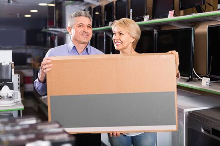 Cheerful  mature couple are happy with choice and purchased consumer electronics for your home Stock Photo