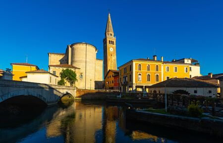 Scenic Portogruaro cityscape on bank on Lemene river overlooking chapel of Madonna della Pesqueria and belfry of Duomo of Sant Andrea in sunny day, Italy