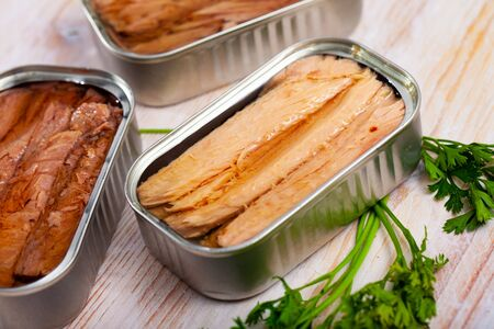 Closeup view of open cans of canned mackerel fish on wooden table