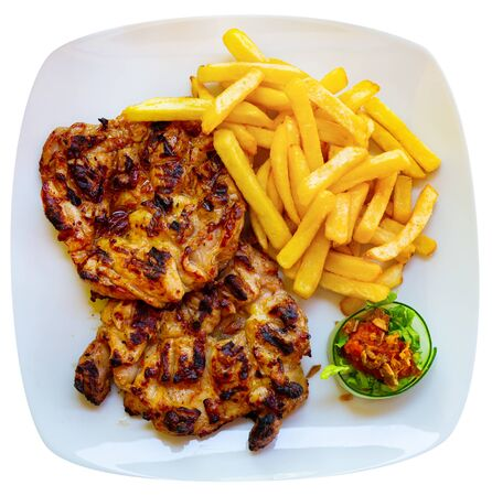 Grilled boneless chicken thighs (Pileci Batak) served with fries and sauce on white plate. Traditional Balkan cuisine. Isolated over white background