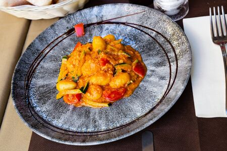 Dumplings from salmon and stew of courgette and tomatoes, served with balsamic