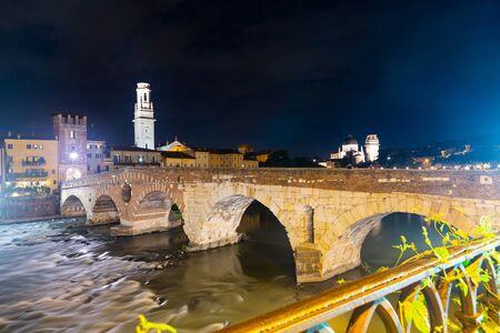 Scenic view of ancient Roman arch bridge Ponte Pietra crossing Adige River in Verona at night, Italy Stock Photo