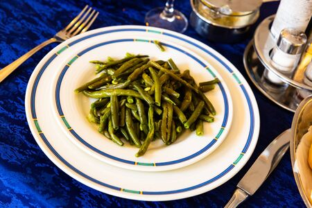 Delicious vegetable garnish of stewed green beans on white plate Banco de Imagens