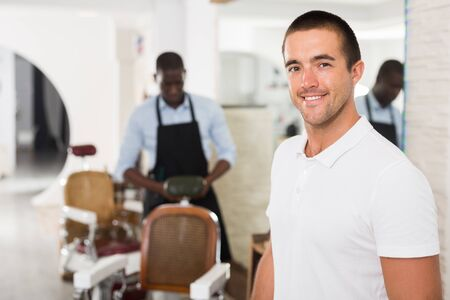Portrait of cheerful young man satisfied with service in professional barbershop