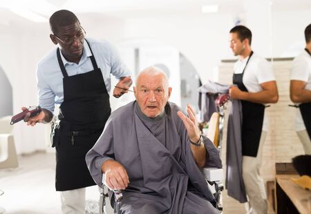 Portrait of upset dazed aged man sitting in barber chair with confused African hairdresser behind him Фото со стока