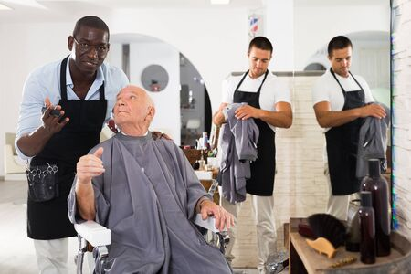 Positive gray-haired male client sitting in hairdressing chair, discussing haircut with African hairdresser Stockfoto