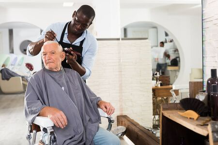 African-American hairdresser doing styling for gray-haired man with hair clipper at barber shop