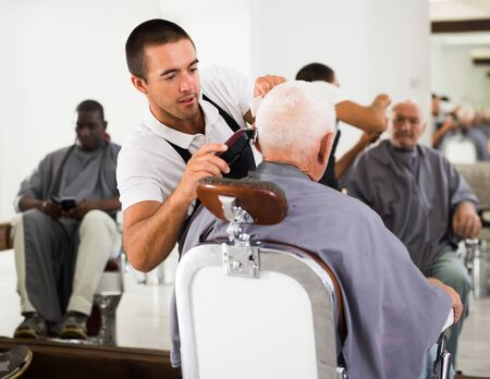 Young hairdresser cutting gray hair of aged male client with electric clipper at barber shop Фото со стока