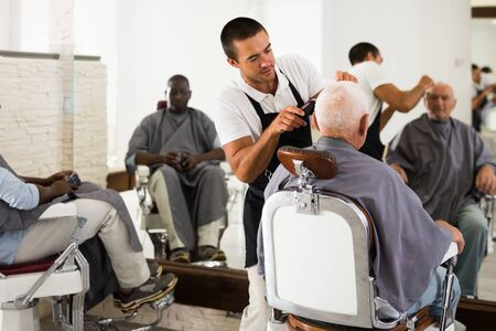 Skillful barber making hairstyle for elderly male client in hair studio, using electric trimmer