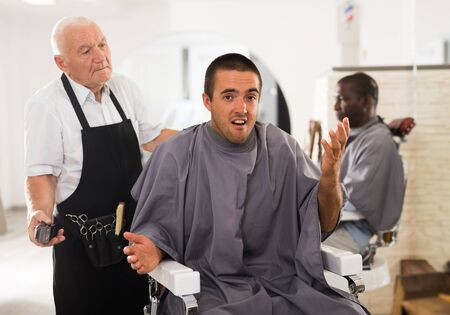 Portrait of shocked male client sitting in barber chair complaining about haircut to confused aged hairdresser
