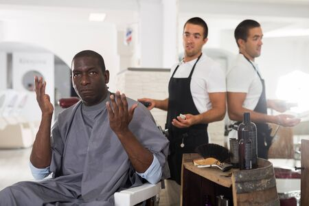 Portrait of shocked African American sitting in barber chair with confused young hairdresser behind him 版權商用圖片 - 130793644