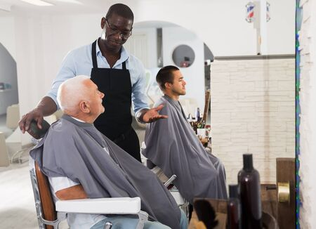 African-American man hairdresser discussing elderly male customer preferences in barbershop before haircut