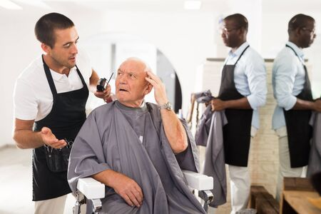 Portrait of shocked elderly man sitting in barber chair with confused young hairdresser behind him 版權商用圖片 - 130793646