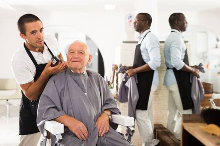 Smiling gray-haired man sitting in hairdressing chair, discussing haircut with young professional barber