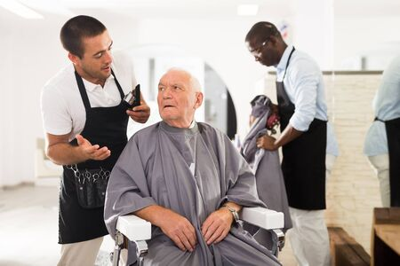 Portrait of shocked elderly man sitting in barber chair with confused young hairdresser behind him