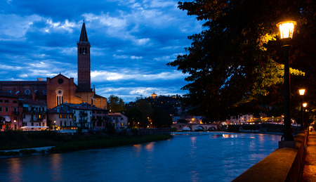 Picturesque view of ancient part of Verona city on bank of Adige River with Gothic building of Dominican church of Saint Anastasia at twilight, Italy