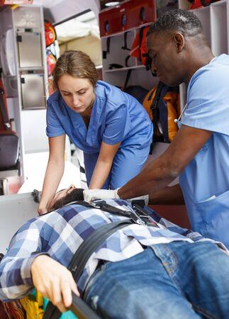 Médicos de emergencia que arreglan al paciente en camilla en ambulancia Foto de archivo