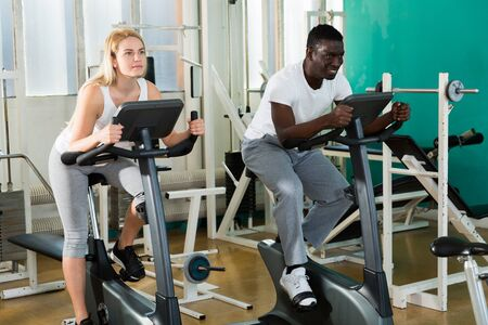 African man and Caucasian woman exercising on stationary bikes at gym