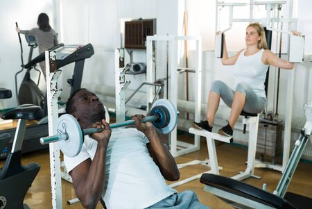 Group of people exercising with weight and on simulators in gym
