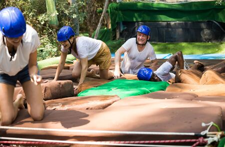Team of friends overcomes an obstacle course in an amusement park Imagens
