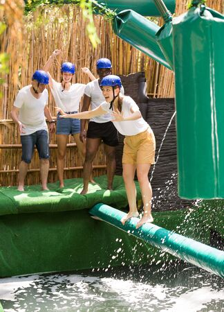 Young people try to walk the wet log in the theme park 版權商用圖片