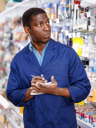 Focused diligent positive cheerful smiling worker of household store making notes while performing inventory of goods