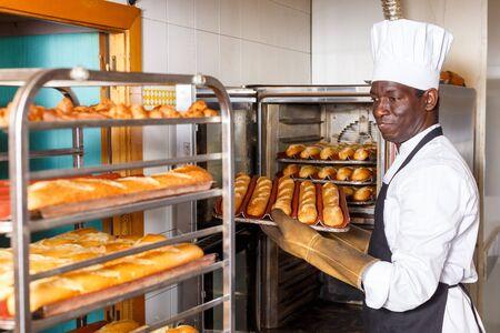 Erfahrener Bäcker, der in einer kleinen Bäckerei arbeitet, Brot aus dem Industrieofen herausnimmt und auf das Gestell legt
