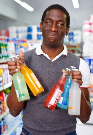 Portrait of happy cheerful  Afro man buying carbonated beverages in store