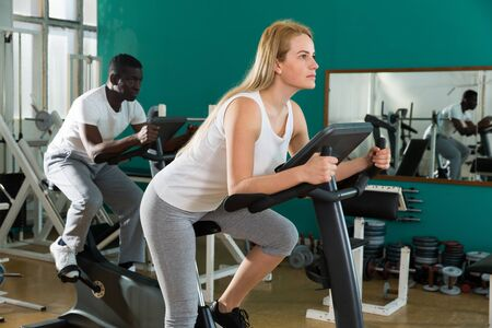 Portrait of couple training on stationary cycles at sport club