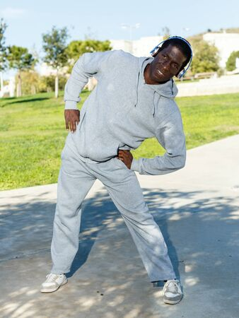 Portrait of active african american man doing workout in park at sunny day