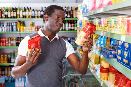 Cheerful glad   afro man standing near rack and choosing pasta in store