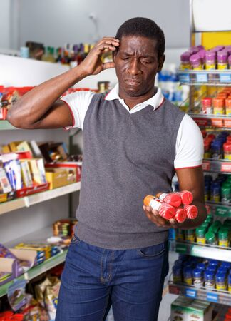 Portrait of sad African man choosing spice from the range in supermarket