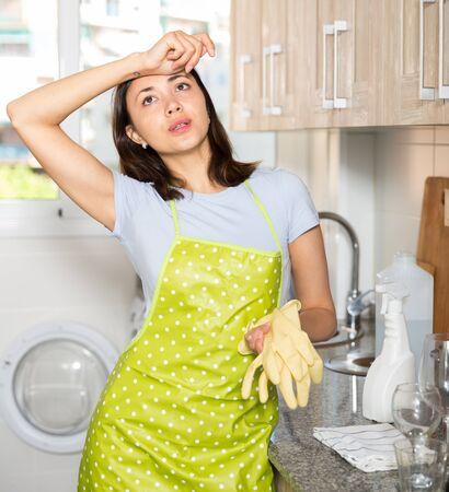 Femme au foyer fatiguée en tablier tenant des gants dans la cuisine à domicile