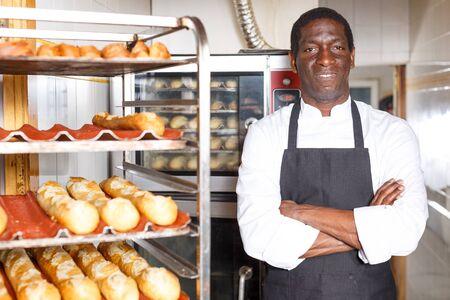 Selbstbewusster Bäcker in schwarzer Schürze, der mit verschränkten Armen in der Nähe eines professionellen Brotbackofens in einer kleinen Bäckerei steht