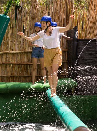 Youth in the amusement park trying to pass through an obstacle course