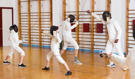 Adults and teens wearing fencing uniform practicing with a foil in the gym