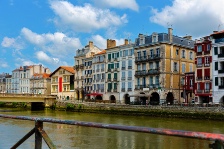 View across Nive river of colorful houses on Bayonne embankment on summer day, France