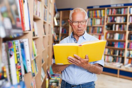 Positive senior man reading new books in bookshop Banco de Imagens