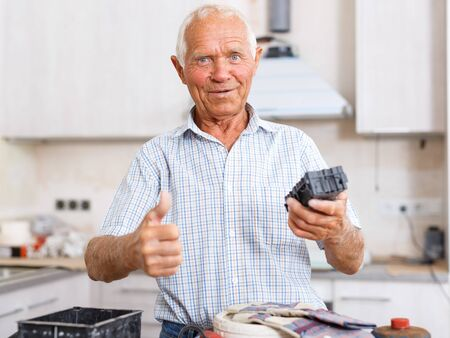 Happy elderly man standing in apartment during overhaul, giving thumbs up 版權商用圖片
