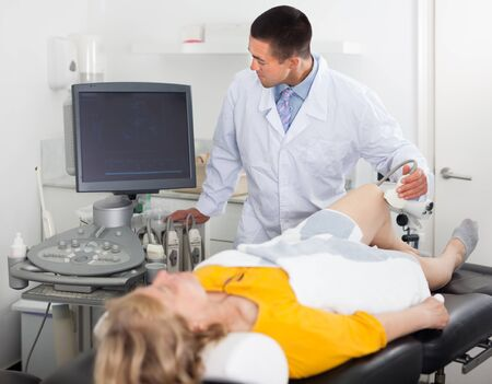 Man during ultrasound test of young woman of knee in hospital