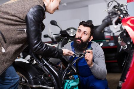 Male worker offering help to female customer to repair motorcycle in workshop