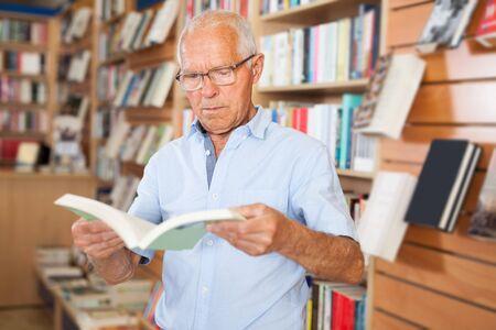 Older man customer browsing inside of books while visiting bookshop Foto de archivo
