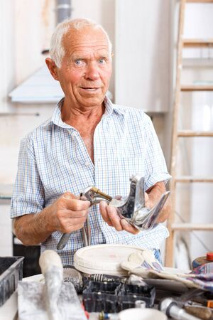 Experienced older man standing with mixer tap in hands in his repairable house