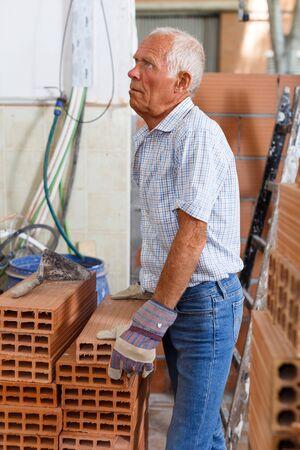 Anciano concentrado trabajando en las renovaciones de su hogar, comprobando ladrillos para mampostería