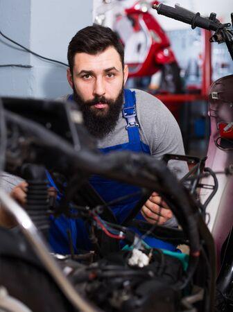 Young man worker working at restoring motorbike in motorcycle workshop