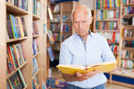 Portrait of older man looking inside of book while visiting bookstore